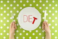 Hands hold flatware above dieting plate Stock Photo