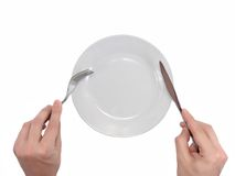 Hands hold fork and knife above plate. Royalty Free Stock Photography