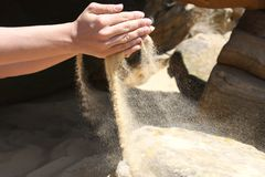 Hands hold a handful of sand and poured it Stock Images