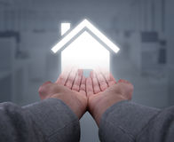 Hands hold home. Two hands, seen firsthand supporting an abstract house Royalty Free Stock Images