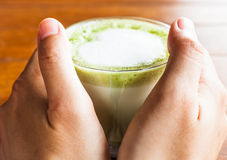 Hands hold hot drink of matcha green tea Stock Photography