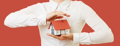 Hands hold house as a household insurance concept. Two female hands are holding a small house as a household contents insurance concept Stock Photos
