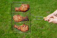 Hands hold a lattice with fried meat Royalty Free Stock Images