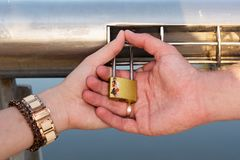 The hands hold the lock buttoned on the railing of the bridge. Two hands hold the lock buttoned on the railing of the bridge Stock Image