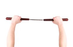 Hands hold martial arts nunchaku. Royalty Free Stock Image