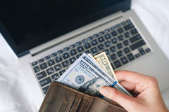 Hands hold money over laptop, internet payments. Unrecognizable person hold money and wallet over laptop, closeup. Internet payments, online shopping, buy on Stock Images