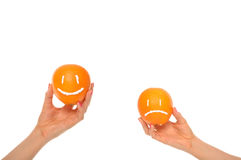 Hands hold oranges with smile and insult Stock Photo
