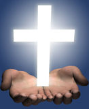 Hands hold out a bright shining white cross Royalty Free Stock Photography