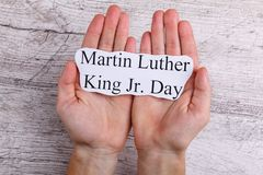 Hands hold on the palms of a paper sign with the inscription Martin Luther King Jr. Day. Hands of a man hold on the palms of a paper sign with the inscription stock images
