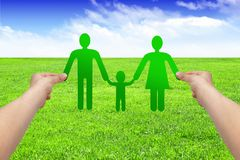 Hands hold paper family on grass, eco concept Stock Photography