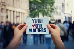Hands hold a paper sheet with the message your vote matters over a crowded street background. People legal and democratic rights,