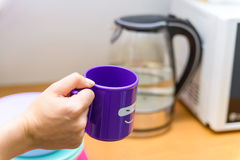 Hands hold plastic cup with smiling face. Close up female hands holding bright violet tea mug with a funny face on it Royalty Free Stock Photography