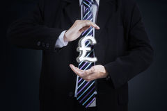 Hands hold a pound currency sign. Businessperson hands holding a pound currency sign and wearing formal suit stock photography