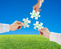 Hands hold puzzles with recycle symbol and beautiful landscape g Royalty Free Stock Photography