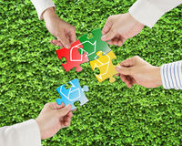 Hands hold puzzles with recycle symbol in fresh meadow backgroun Royalty Free Stock Images