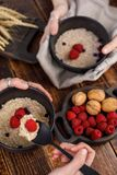 Hands that hold refined ceramic bowls with oatmeal and fresh raspberries. Still life on a wooden background and textiles Royalty Free Stock Photo