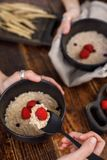 Hands that hold refined dishes with oatmeal and fresh raspberries. Still life on a wooden background and textiles Royalty Free Stock Images