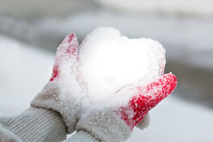 Hands hold snow like a heart Royalty Free Stock Photos