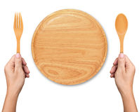 Hands hold spoon and fork with Empty wood plate on white. Background Royalty Free Stock Photo