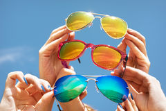 Hands hold sunglasses on sky blue background concept friends. Hands hold three sunglasses on blue backdrop of sky Royalty Free Stock Photography