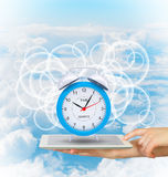Hands hold tablet pc with alarm clock. Blue sky background Royalty Free Stock Image