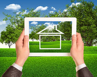 Hands hold tablet pc. House icon on touch screen. Business concept Stock Photo