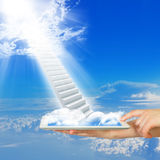 Hands hold tablet pc with stairs in sky Royalty Free Stock Image