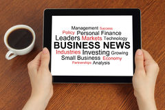 Hands hold tablet PC with tag cloud of business news Royalty Free Stock Photo