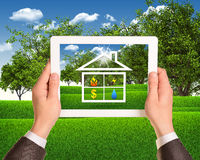 Hands hold tablet with symbols of public service. Hands hold tablet pc with symbols of public service and house. Landscape as backdrop Stock Photos