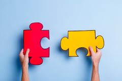 The hands hold two puzzles. On a blue background. The hands of the European man hold two large puzzles. On a blue background Royalty Free Stock Images