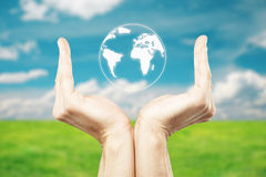 Hands holding abstract globe. Male hands holding abstract terrestrial globe on beautiful landscape background Stock Photo