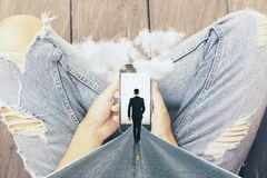 Hands holding abstract smartphone. With walking businessman, road and clouds on wooden floor background. Imagination and dream concept Royalty Free Stock Photos