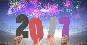 Hands holding 2017 against composite image of fireworks in 3D stadium. Hands holding 2017 against composite image of fireworks in 3D  stadium at night Stock Images