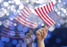 Hands holding american flags against shiny background. Digital composite of Hands holding american flags against shiny background Stock Images