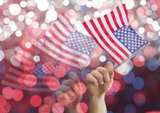 Hands holding american flags against shiny background. Digital composite of Hands holding american flags against shiny background Stock Photography