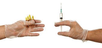 Hands holding ampules with yellow drug and syringe Stock Image