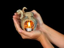 Hands holding aromalamp. Female hands holding aromatherapy lamp, isolated on a black background stock image