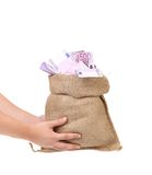 Hands holding bag full with euro bills. Royalty Free Stock Photo