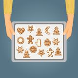 Hands holding baking tray with christmas cookies Stock Image