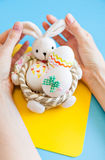 Hands holding basket with Easter eggs Royalty Free Stock Photos
