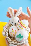 Hands holding basket with Easter eggs Royalty Free Stock Image