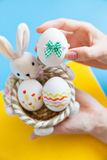 Hands holding basket with Easter eggs Stock Photos