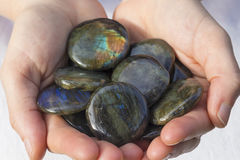 Hands holding beautiful labradorite pieces royalty free stock photo