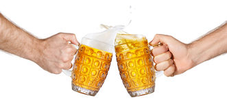 Hands holding beer mugs making toast. Two mugs of beer toasting creating splash isolated on white background. Pair of male hands holding beer mugs making toast Stock Photography