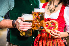 Hands holding Beer and Pretzels, detail of bavarian Tracht Stock Images