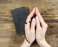 Hands holding the Bible and praying with a rosary Stock Photos