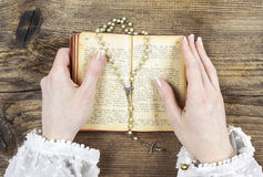 Hands holding the Bible and praying with a rosary Royalty Free Stock Image