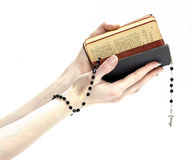 Hands holding the Bible and praying with a rosary Royalty Free Stock Photos