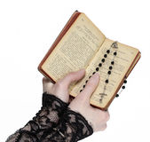 Hands holding the Bible and praying with a rosary Royalty Free Stock Images