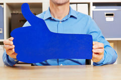 Hands holding big blue thumbs up. In an office stock photography